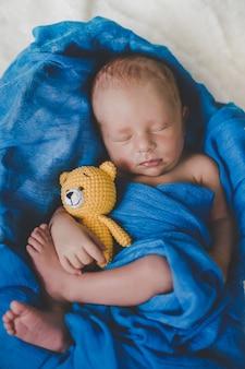Un bebé recién nacido duerme con un osito de peluche.
