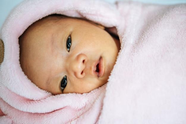 Bebé recién nacido duerme sobre la manta y abre los ojos