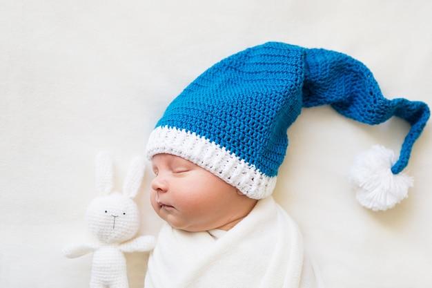 Bebé recién nacido durmiendo en un gorro de navidad con conejito de ganchillo sobre un fondo blanco.