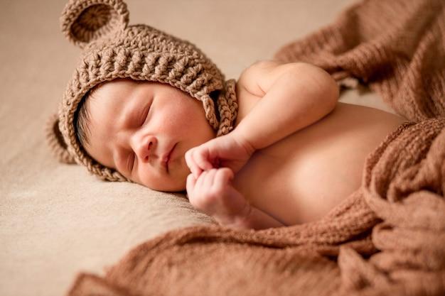Bebé recién nacido durmiendo en gorro de punto se encuentra en tela marrón.