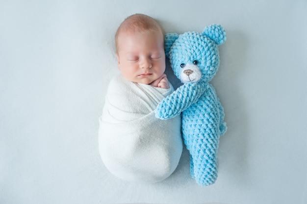 Bebé recién nacido durmiendo sobre un fondo blanco con un oso azul de peluche envuelto en un pañal