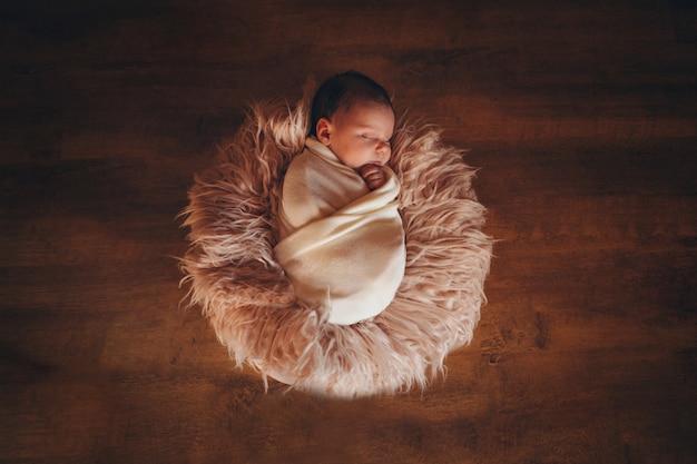 Bebé recién nacido envuelto en una manta durmiendo en una canasta. concepto de infancia, asistencia sanitaria, fiv