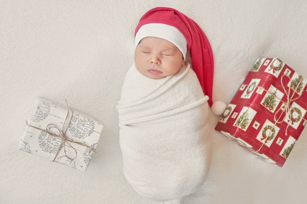 Bebé recién nacido niña santa sobre un fondo claro