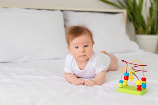 Bebé recién nacido niño descansando en la cama. el niño se acuesta boca abajo en la cama con un juguete. infantil