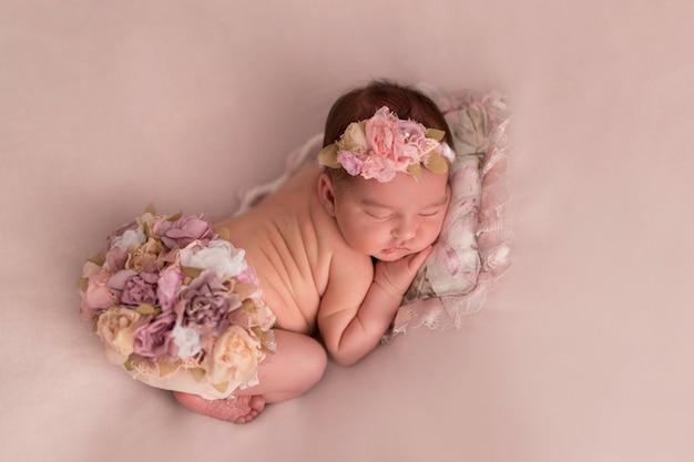 Bebé recién nacido en pantalones cortos florales durmiendo sobre una almohada en la cama