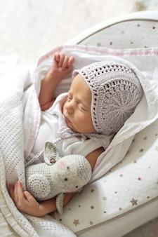 Bebé recién nacido que duerme con el juguete en el pañal en capullo