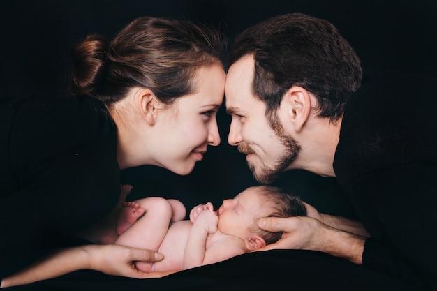 Bebé recién nacido que miente en las manos de padres en un fondo negro. imitación de un bebé en el útero.
