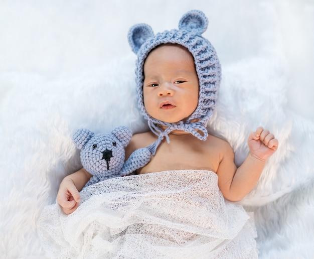 Bebé recién nacido en sombrero de oso en la cama de piel
