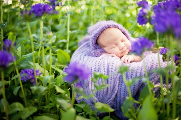 El bebé recién nacido sonriente de 17 días duerme boca abajo en la cesta en la naturaleza en el jardín al aire libre.