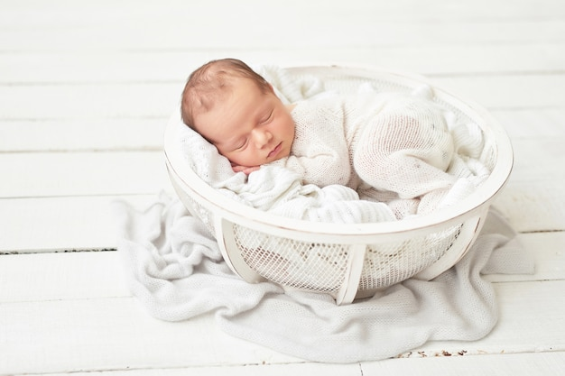 Bebé recién nacido en un traje blanco en la cuna