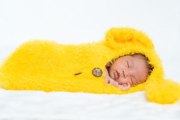 Bebé recién nacido en traje de piel de conejo durmiendo en una cama