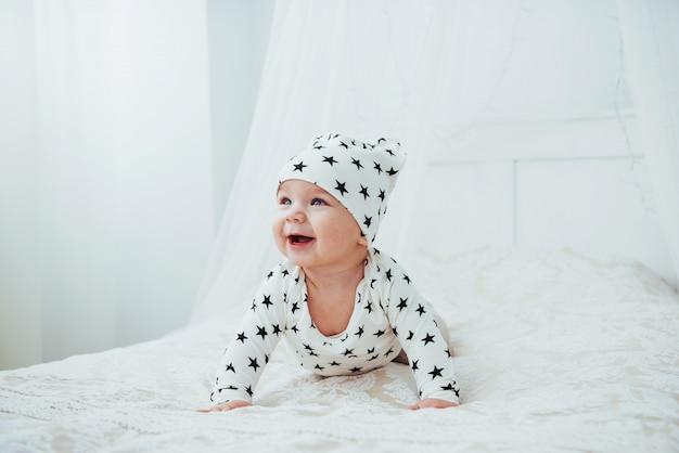 Bebé recién nacido vestido con un traje blanco y estrellas negras es una cama blanca suave en el estudio