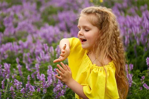 Bebé con rizos sentado en el campo, sosteniendo una mariquita, vestida con un vestido amarillo, tarde de verano