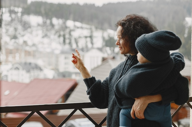 Bebé en ropa de abrigo. abuela de pie con su nieta. vacaciones en la montaña en invierno