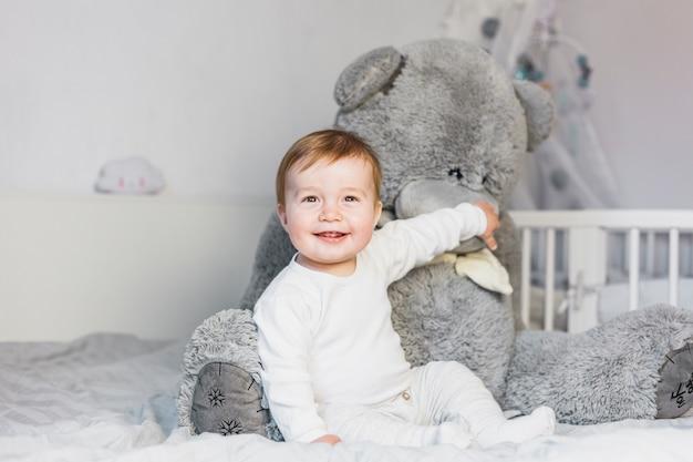Bebé rubio adorable sobre cama blanca con oso de peluche