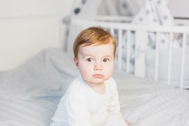 Bebé rubio adorable sobre cama blanca