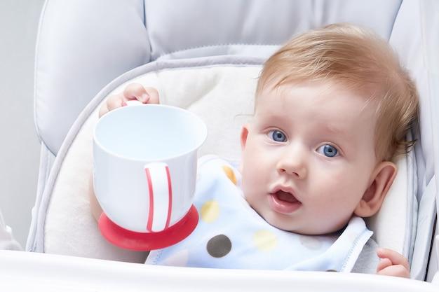 El bebé rubio come el primer señuelo. sosteniendo un bebedor cerrar