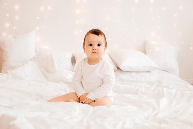 Bebé sano de 10 meses de edad con ropa blanca sonriendo sentado en ropa de cama blanca en la cama, espacio para texto