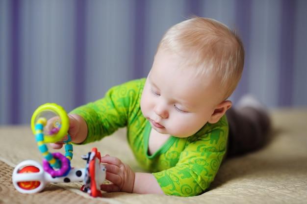 Bebé de seis meses jugando con juguetes brillantes.