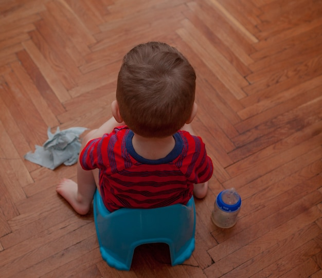 Bebé sentado en el orinal con papel higiénico y chupete en un piso marrón.
