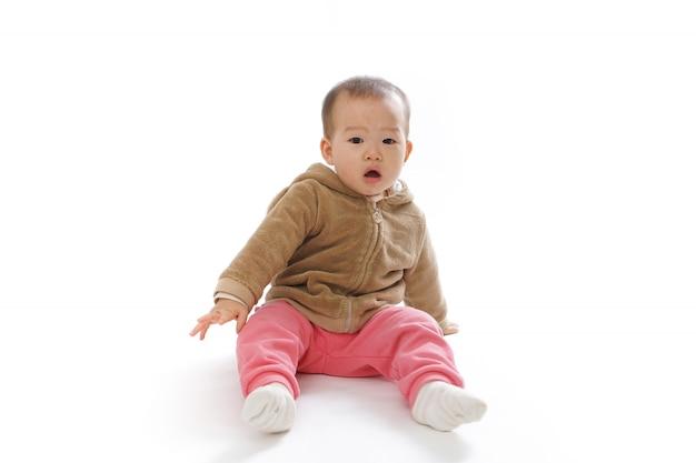 Bebé sentado en el suelo jugando en blanco