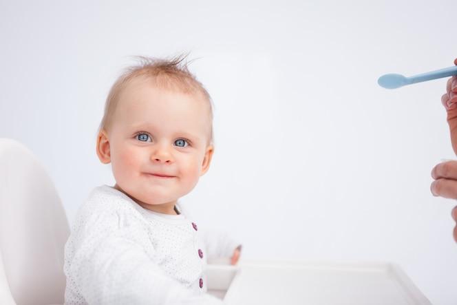 Bebé sonriente mirando a la cámara mientras se alimenta contra un fondo gris