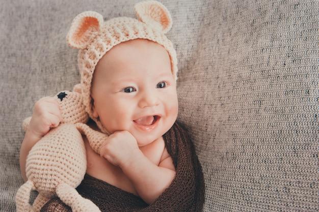 Bebé sonriente de ojos claros. un niño pequeño con una gorra beige con orejas y un juguete beige tejido en la mano.