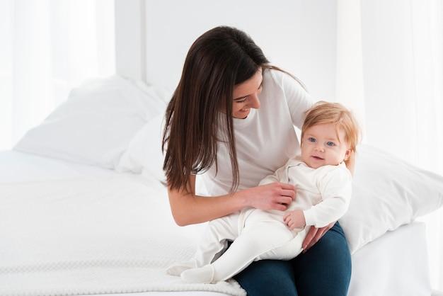 Bebé sonriente retenido por la madre