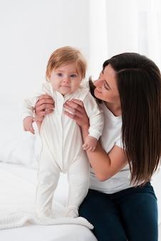 Bebé sonriente sostenido por la madre y posando