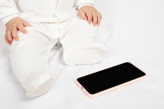 Bebé sosteniendo un teléfono móvil aislado en la generación de fondo blanco z