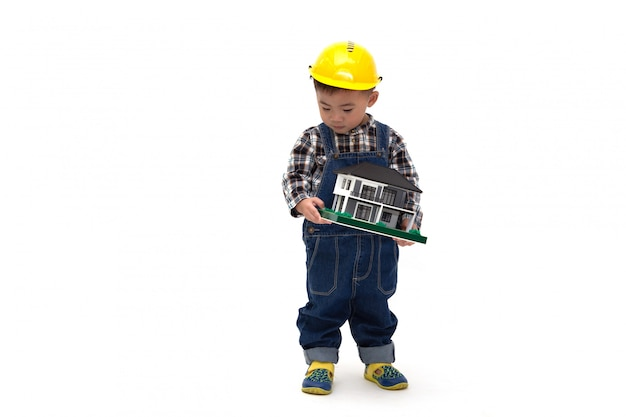 Bebé tailandés asiático vistiendo un traje de ingeniero con casco y sosteniendo una casa de muestra aislada, trabajador de la construcción