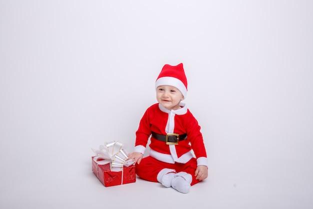 Un bebé en un traje de santa claus sobre un fondo blanco.
