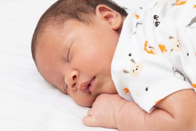Bebé tranquilo y relajado, durmiendo en la cama. vista superior.