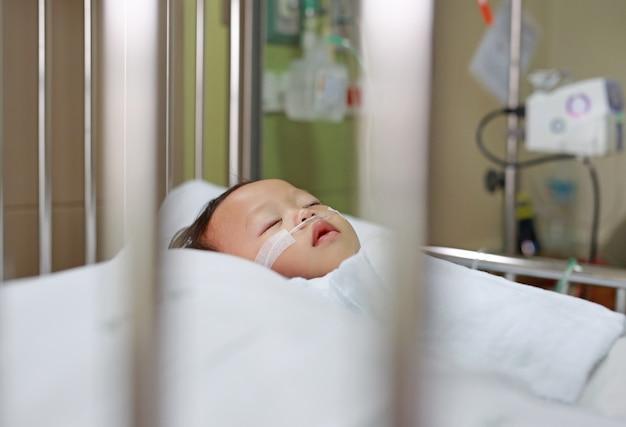 Bebé con tubo de respiración en nariz recibiendo tratamiento médico.