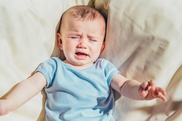 Bebé tumbado al sol enojado y llorando llamando a sus padres.