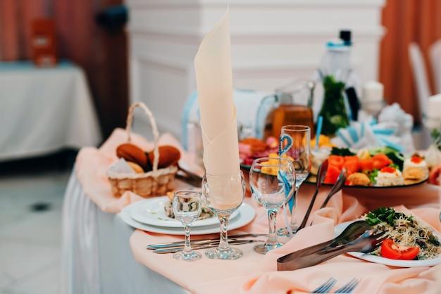 Bebe vasos y comida en la mesa para una cena de gala romántica en el restaurante.