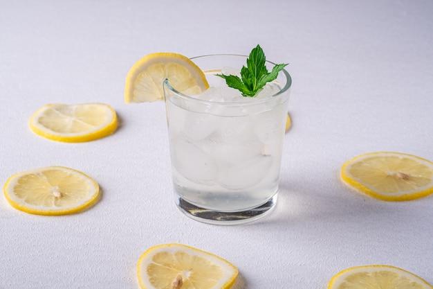 Beber agua fresca fría en vaso con cubitos de hielo, rodaja de limón y hojas de menta cerca de rodajas de limón