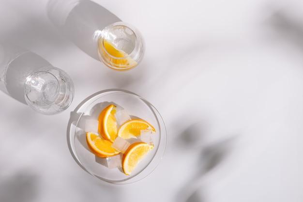 Beber agua natural y hielo en hermosos vasos de vidrio y una rodaja de naranja fresca
