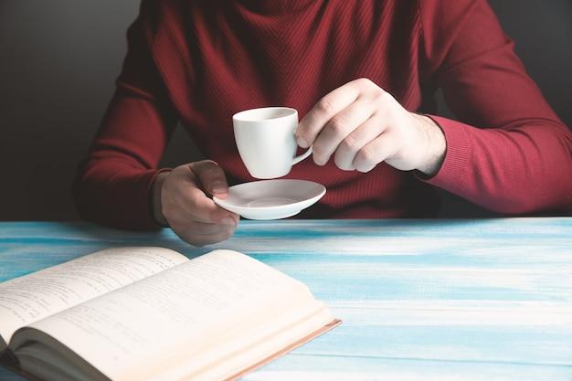 Beber café y leer un libro sobre la mesa