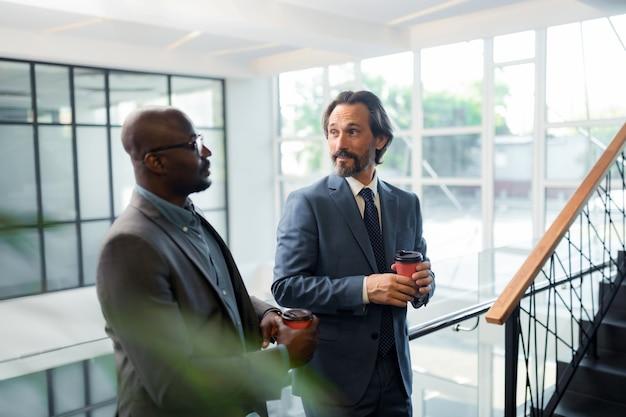 Beber café para llevar. compañeros de trabajo bebiendo café para llevar en la mañana de pie en un amplio centro de negocios