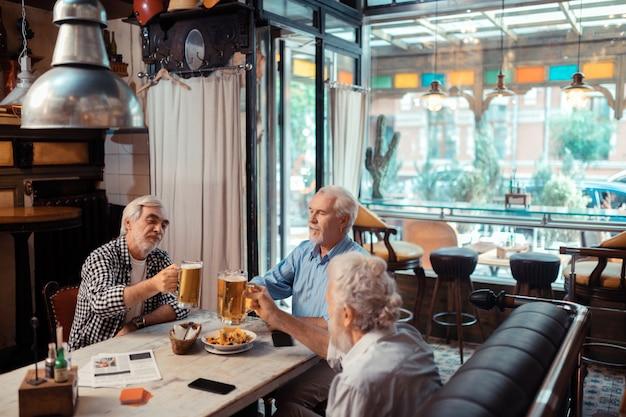 Beber cerveza juntos. tres hombres que se sienten bien mientras beben cerveza juntos en el pub