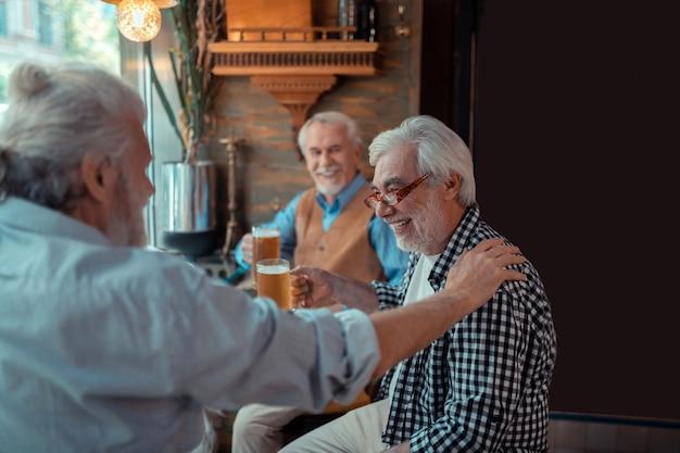 Beber cerveza juntos. viejo amigo tocando el hombro del hombre mientras bebe cerveza juntos en el pub