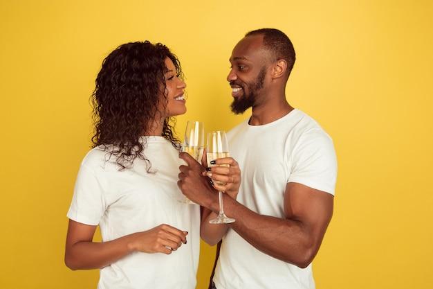 Beber champán. celebración del día de san valentín, feliz pareja afroamericana aislada sobre fondo amarillo de estudio. concepto de emociones humanas, expresión facial, amor, relaciones, vacaciones románticas.