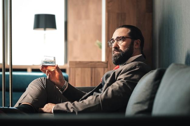 Beber coñac. hombre maduro de pelo oscuro barbudo bebiendo copa de coñac después de la negociación