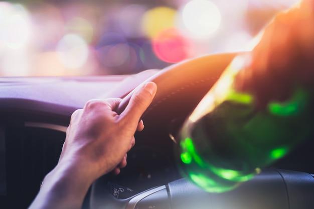 Beber y conducir, hombre bebiendo alcohol mientras conduce un automóvil después de la fiesta por la noche