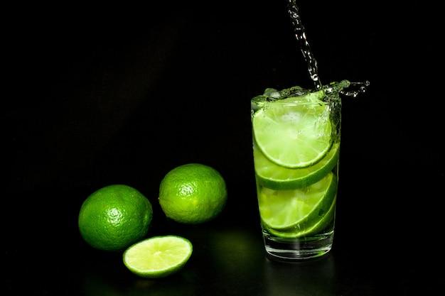 Beber con hielo y limas verdes maduras frescas en negro