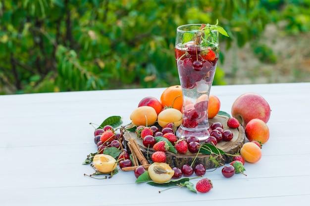 Beber en un vaso con frutas, especias, vista lateral de la tabla de cortar sobre fondo de madera y jardín
