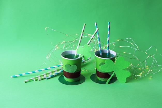Beber en vasos de papel con forma de sombrero de san patricio con pajitas, trébol e iluminación