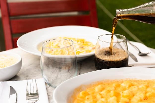 Beber vertiendo en el vaso con sabrosa comida italiana pasta en la mesa en el restaurante
