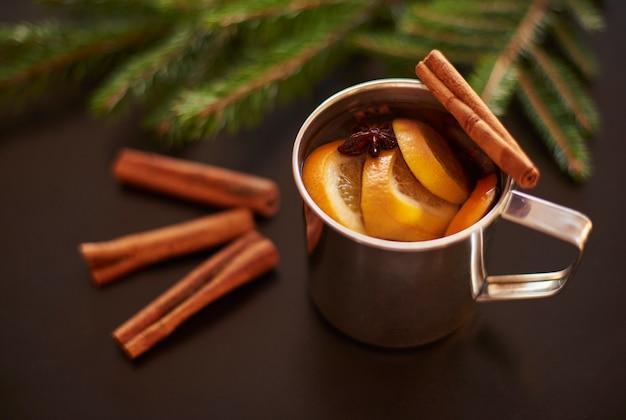 Beber vino caliente sobre mesa negra con ramas de pino